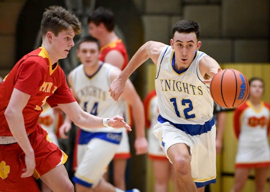Castle's Alex Hemenway (12) leads a fast break past Mater Dei's Jackson Hiester (33) as the Mater Dei Wildcats play the Castle Knights in Paradise Tuesday, January 22, 2019.