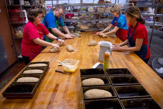 Loaves of Dakota bread are shaped for baking at Great Harvest Bread Co. at 423 Metro Avenue Wednesday morning. The bakery is one of many local businesses who are offering help to government employees feeling the effects of  the partial government shutdown. Those pictured are, from left, co-owner Katie Riney, Jacob Steele, Patti McCrory and Linda Fink.