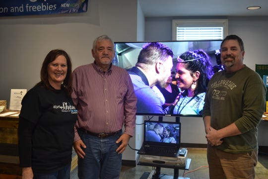 Left to right are New Hope Vineyard Church Associate Pastor Nancy Cullen, Ron Conner, and Lead Pastor Tony Buxsel, who stand next to a video promoting the Night to Shine event, one of the ministries of the Tim Tebow Foundation.