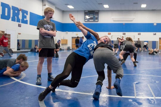 Poudre High School junior wrestler Elise Justine Golyer spars with freshman Tony Garcia-Lopez while teammate Liam Oberschmidt waits for his turn to rotate in during a practice on Tuesday, Jan. 22, 2019, Poudre High School in Fort Collins, Colo.