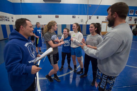 Poudre High School wrestlers from center-left, Maya Beck-Kjer, Elise Justine Golyer, Maggie Moseley and Elizabeth Esparza laugh with coach Barret Golyer, left, and assistant coach David Cummings during a practice on Tuesday, Jan. 22, 2019, Poudre High School in Fort Collins, Colo.