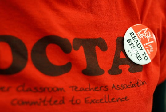 In this Thursday, Jan. 17, 2019, file photo, a teacher wears a button on a union shirt in the Denver Classroom Teachers Association, the union's headquarters in south Denver. Teachers voted Tuesday to authorize a strike, which would be the first called in 25 years in the state's largest school district. (AP Photo/David Zalubowski, File)