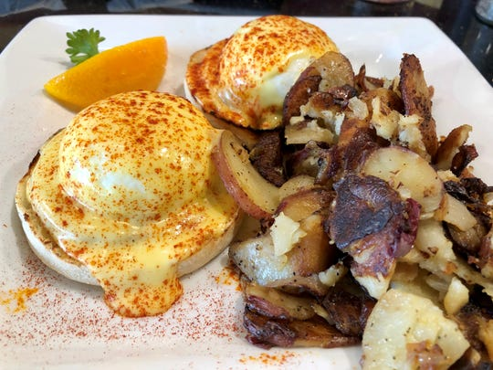 Traditional eggs Benedict with home fries from Keke's Breakfast in Cafe Cape Coral.