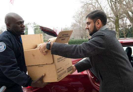 Javaid Qazi, from the Islamic Society of Greenville, delivers meals for TSA employees to Sammuel Jean, a TSA supervisor, at Greenville–Spartanburg International Airport Wednesday, Jan. 23, 2019.