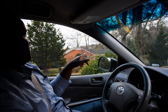 Melchior Julien points to a home with a shed tucked away behind trees and shrubs in his neighborhood on Tuesday, Jan. 22, 2019. Julien says he has been in ongoing legal battles with his HOA over the construction of a sunroom and a temporary shed he had in his yard to store building materials but says he isn't the only resident to have such structure in his neighborhood.