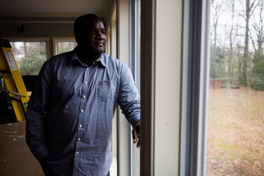 Melchior Julien looks out of one of the windows of his new sunroom on Tuesday, Jan. 22, 2019. Julien has been fighting his local HOA over its construction and believes he has been singled out over other residents who have similar structures on their property.