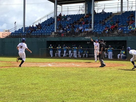 American Samoa's Luke Pagua gets the sign to cruise into home plate after scoring a run in the fifth inning to make it 10-2 in U18 Oceania Baseball Championship action over Palau Jan. 23 at the Paseo Stadium.