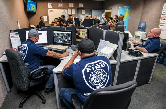Guam Fire Department Emergency Medical Dispatchers Roy Ignacio, left, Christian Cruz and others, monitor their stations within the 911 Dispatch Center as Gov. Lou Leon Guerrero and Lt. Josh Tenorio tour the Guam Homeland Security - Office of Civil Defense facility in Agana Heights, on Wednesday, Jan. 23, 2019.