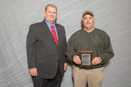 Kentucky Soybean Promotion Board Chair Ryan Bivens (left) presents Philip Meredith with his wife Lea's second place plaque for the state irrigated soybean yield contest. Mrs. Meredith's entry was 92.37 bushels per acre.