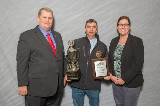 Kentucky Soybean Promotion Board Chair Ryan Bivens, at left, and UK's Carrie Knott present Waller Brothers' Jerrod Murphy of Union County with the State Champion Award in the Kentucky Soybeans Contest at the 2018 Crop Production Awards Banquet held in Bowling Green.