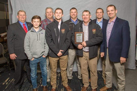 Kentucky Soybean Promotion Board Chair Ryan Bivens (back row, left) presents the second place plaque for the state non-irrigated soybean yield contest. The Greenwell Farms entry was 105.08 bushels per acre, earning them entry into the prestigious 100 Bushel Club. In the front row are David, Redmond, Jason and Kirk Greenwell. In back are Ralph, Bryan and Drew Greenwell.