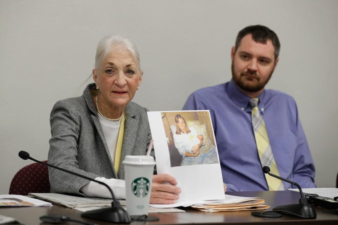 Liz White displays a photo of herself holding Matt White (right) after giving birth. She spoke during a news conference before a committee hearing at the Statehouse Wednesday.