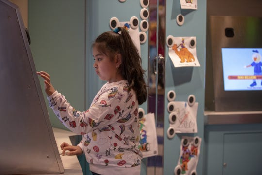 Isabel Perez, 8, Whiting, plays with a display at the Mascot Hall of Fame.