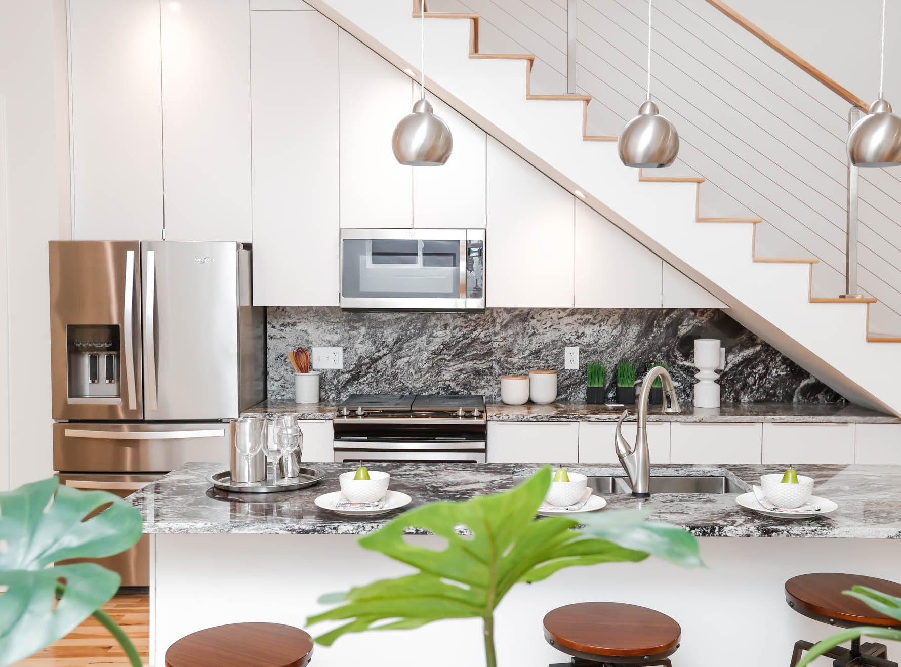A newly built modern architectural home up for sale at 1134 Woodlawn Ave., Indianapolis, Ind., 46203, in the heart of the historic Fountain Square neighborhood, features an open plan concept with white cabinets and stainless steel appliances on Wednesday, January 23, 2019. The three-story home, which features 2,030-square-feet and an open space concept tile and hardwood floors are priced at $479,900.