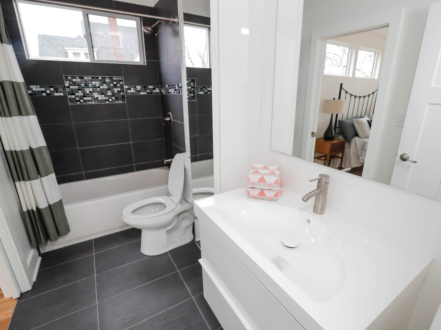 A second floor full bathroom features tile, and a floating vanity inside a newly built modern architectural home up for sale at 1134 Woodlawn Ave., Indianapolis, Ind., 46203, in the heart of the historic Fountain Square neighborhood on Wednesday, January 23, 2019. The three-story home, which features 2,030-square-feet and an open space concept tile and hardwood floors are priced at $479,900.