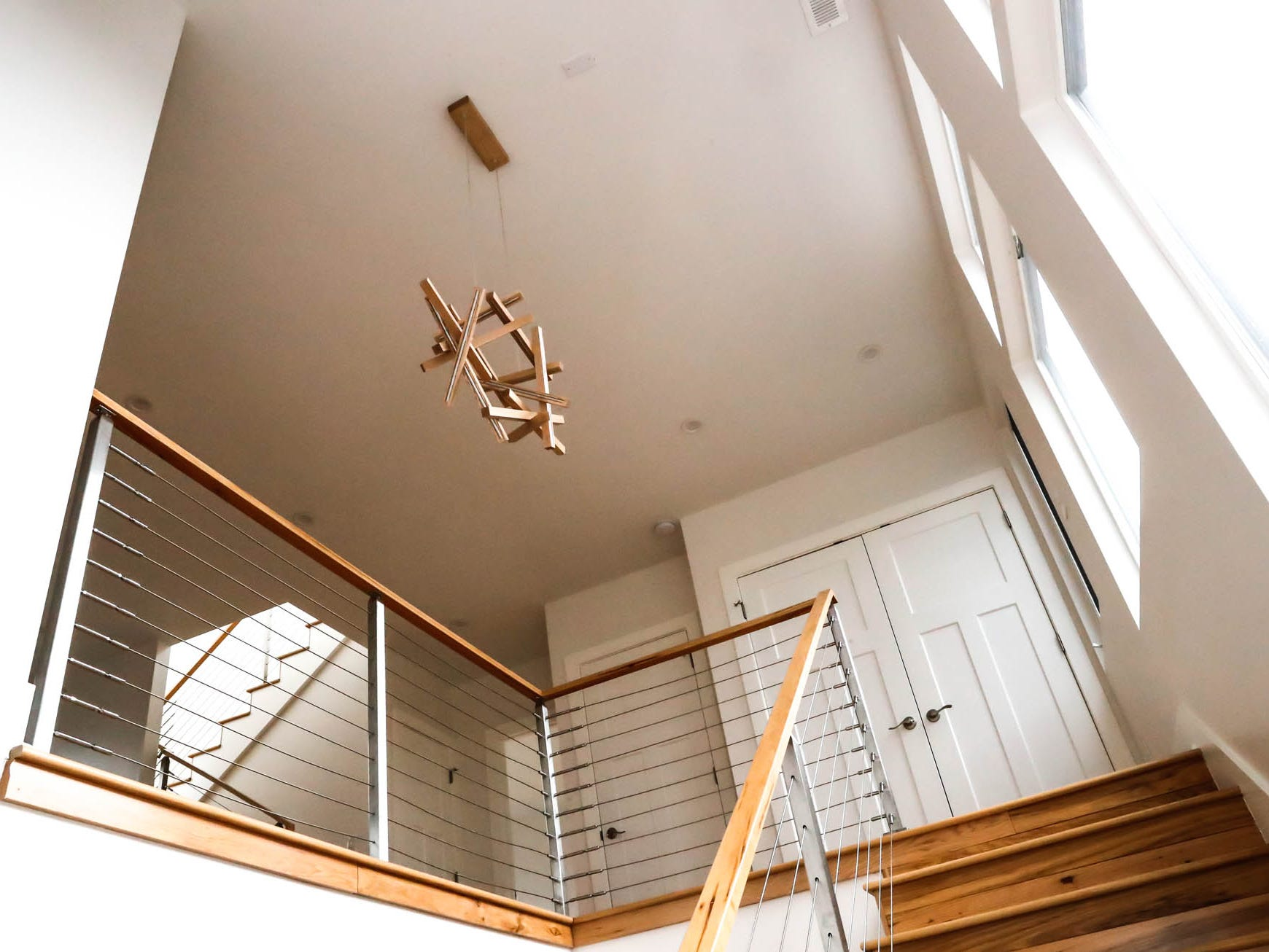 A modern chandelier hangs in an open stairwell Inside a newly built modern architectural home up for sale at 1134 Woodlawn Ave., Indianapolis, Ind., 46203, in the heart of the historic Fountain Square neighborhood on Wednesday, January 23, 2019. The three-story home, which features 2,030-square-feet and an open space concept tile and hardwood floors are priced at $479,900.