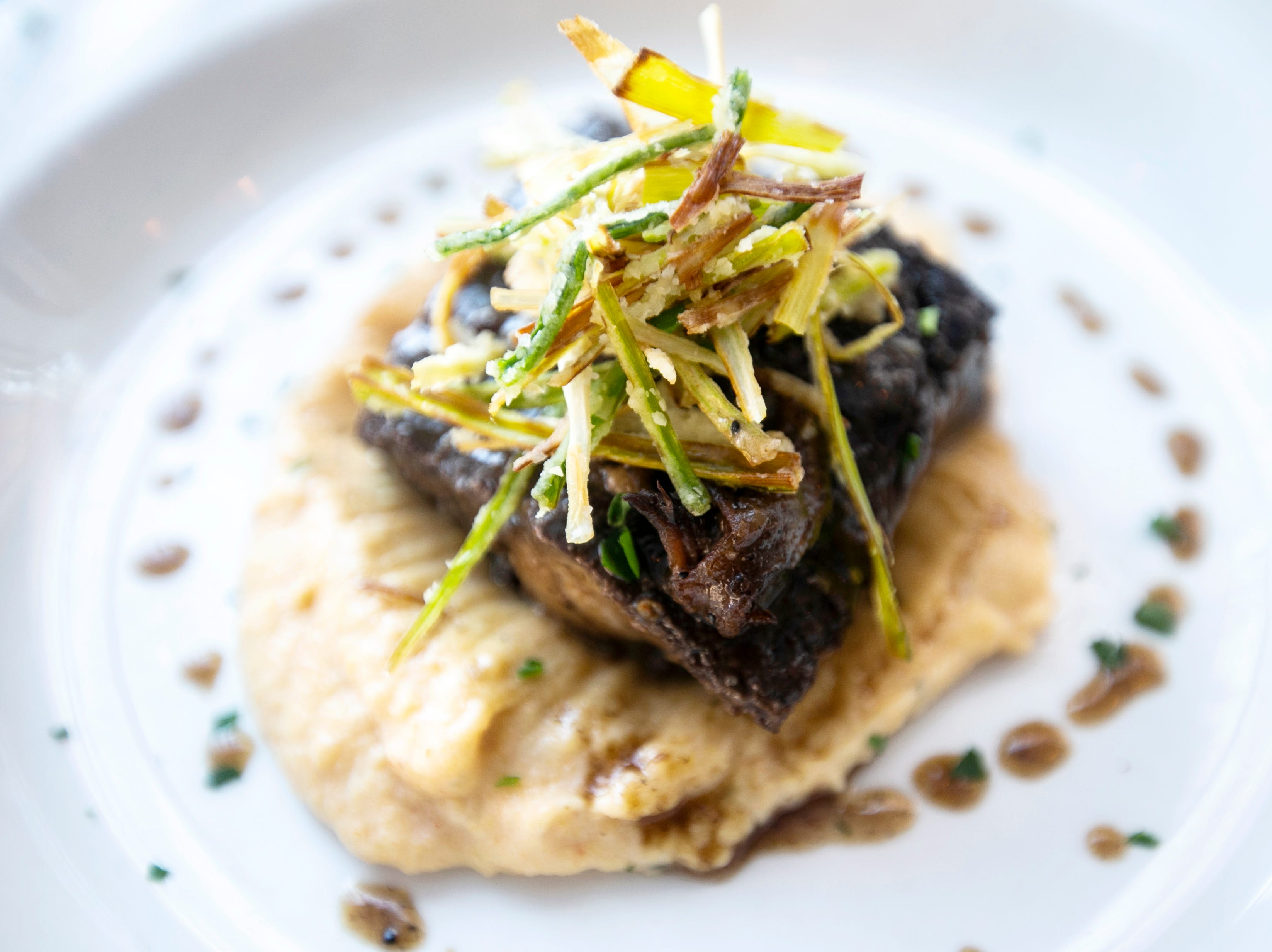 Braised short ribs are seen on Wednesday, Jan. 23, 2019, at Linn Street Dive in Iowa City, Iowa. The entrée is served with anson mills creamy stone-ground polenta and leek frittes.