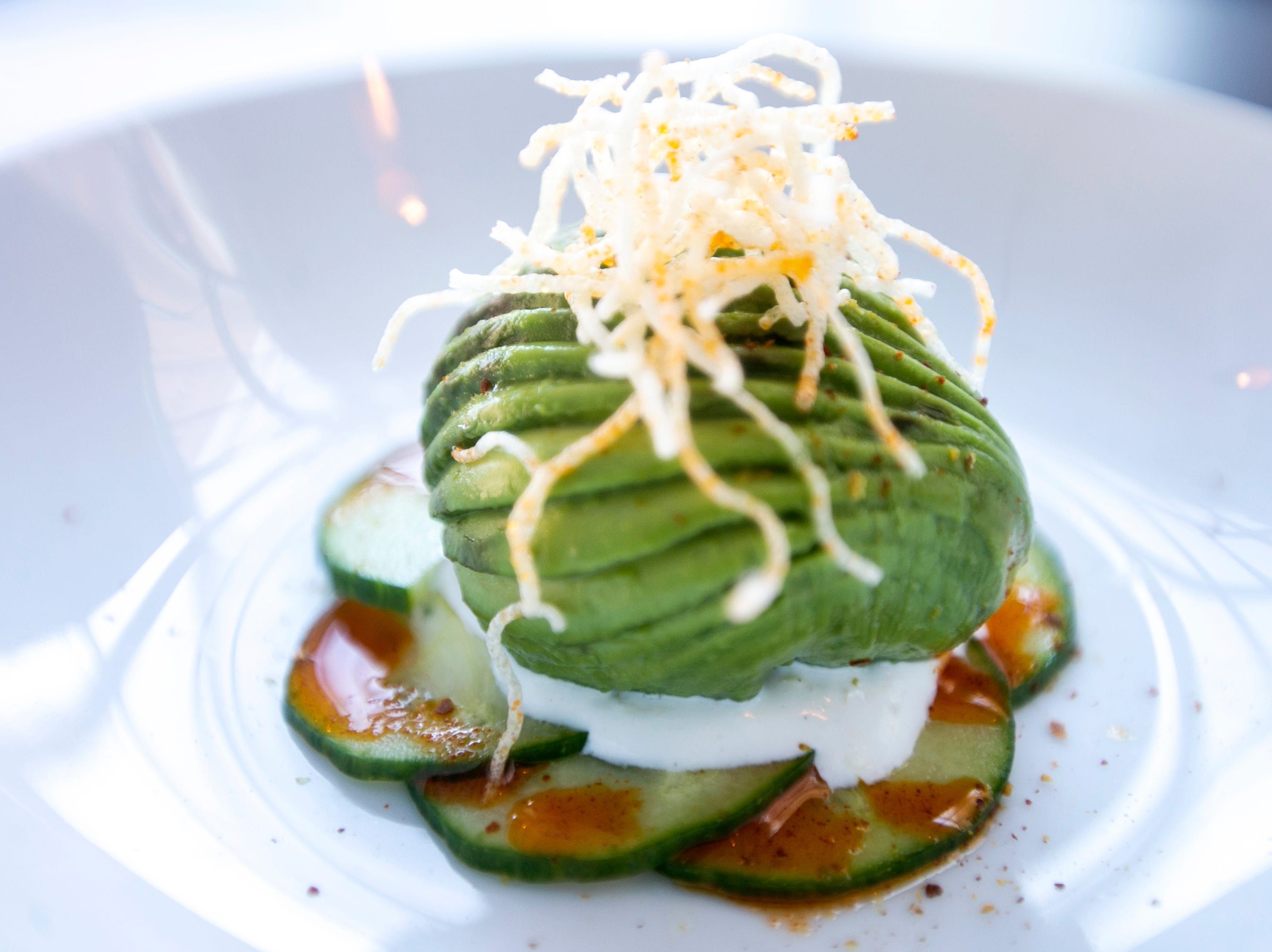 Avocado ravioli is seen on Wednesday, Jan. 23, 2019, at Linn Street Dive in Iowa City, Iowa. The small plate starter is served with salmon gravlax, marinated cucumber, dill creme fraiche and chili oil.