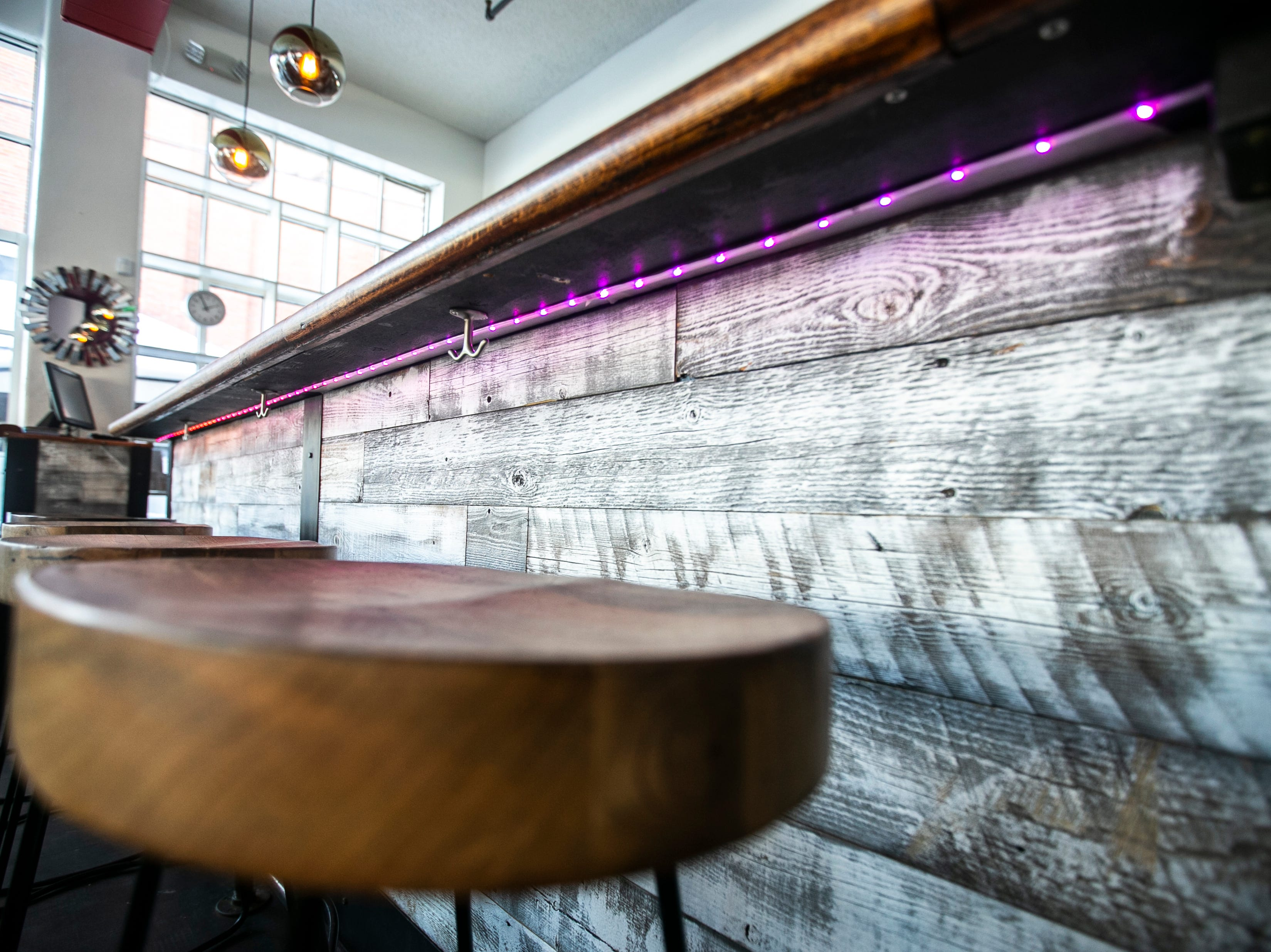 Bar stools are seen opposite an LED light strip running the length of the bar on Wednesday, Jan. 23, 2019, at Linn Street Dive in Iowa City, Iowa.