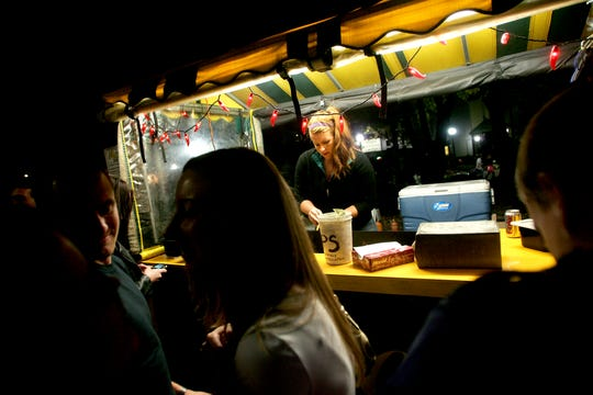 Jill Hoffman works the Marco's Grilled Cheese cart early Sunday morning as patrons begin to head home after the downtown bars close in the ped mall in downtown Iowa City on Saturday night, October 16, 2010.