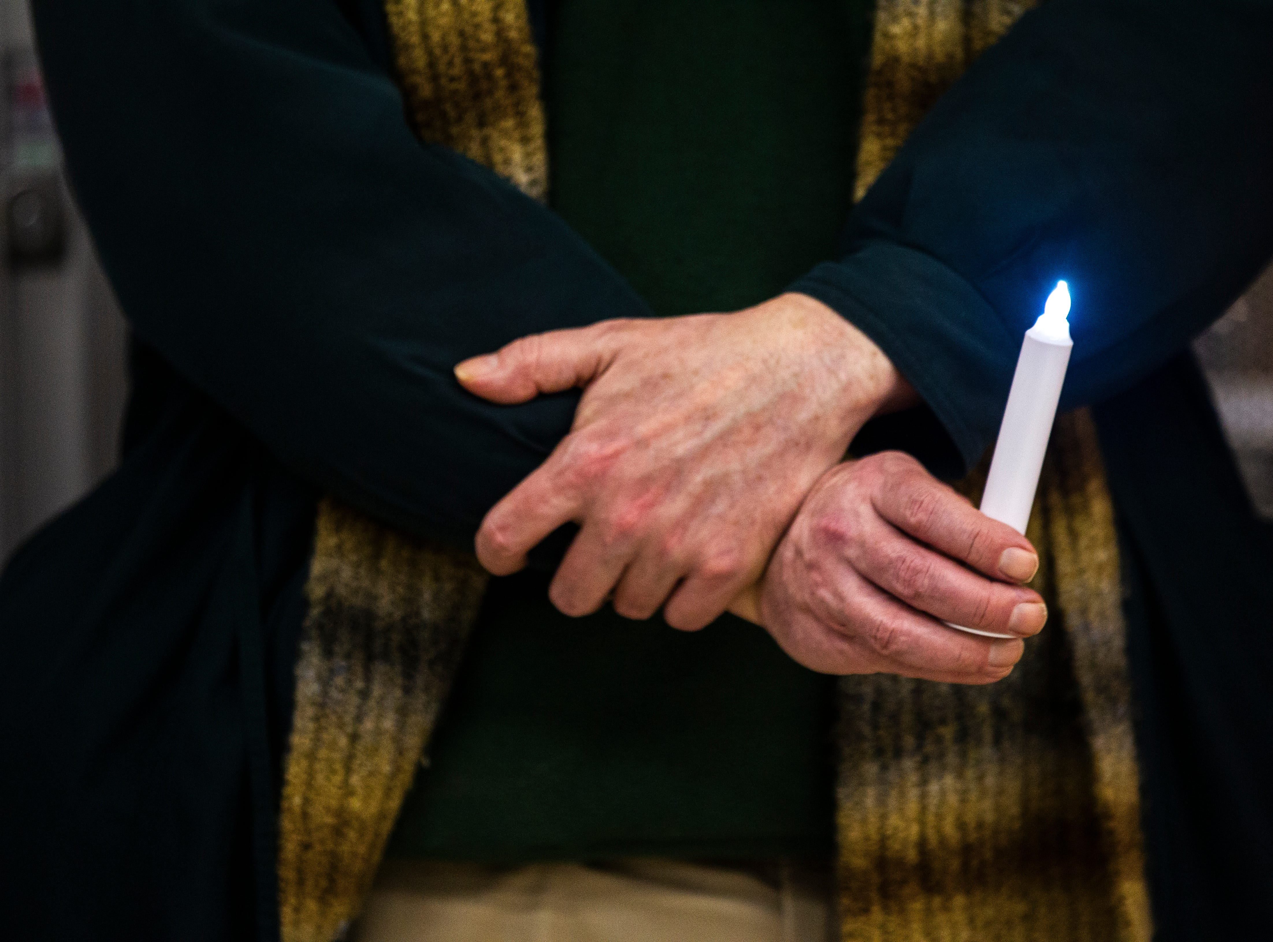 "A person holds a light during the ""Prayer Vigil to Put The Poor First"" after a council work session on Tuesday, Jan. 22, 2019, in the lobby of City Hall in Iowa City, Iowa."