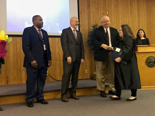 Graduate Bobbie Brooks shakes hands with Circuit Court Judge Russell Lee Moore after receiving her diploma at the Jackson Day Reporting Center graduation ceremony on Jan. 23 in Jackson, Tenn.