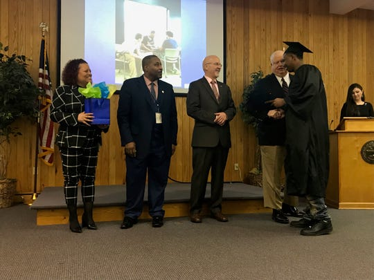 April Buckner, Henry Holiday, Edward Welch and Russell Lee Moore shake graduate Jimmy Deberry's hand at the Jackson Day Reporting Center graduation ceremony on Jan. 23 in Jackson, Tenn.