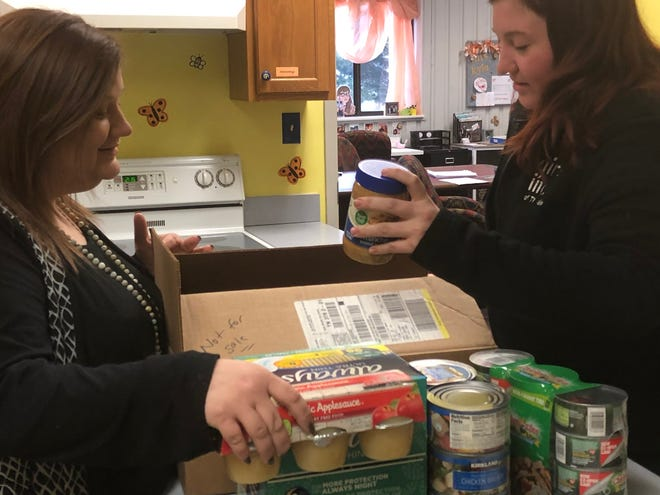 Kyla Black (left) and Meghan Bryge (right), staff members at Girls Inc. of the Tennessee Valley, sort non-perishable food for families affected by the government shutdown. Girls Inc. created its own food pantry from donations to assist families and shift demand from food banks.