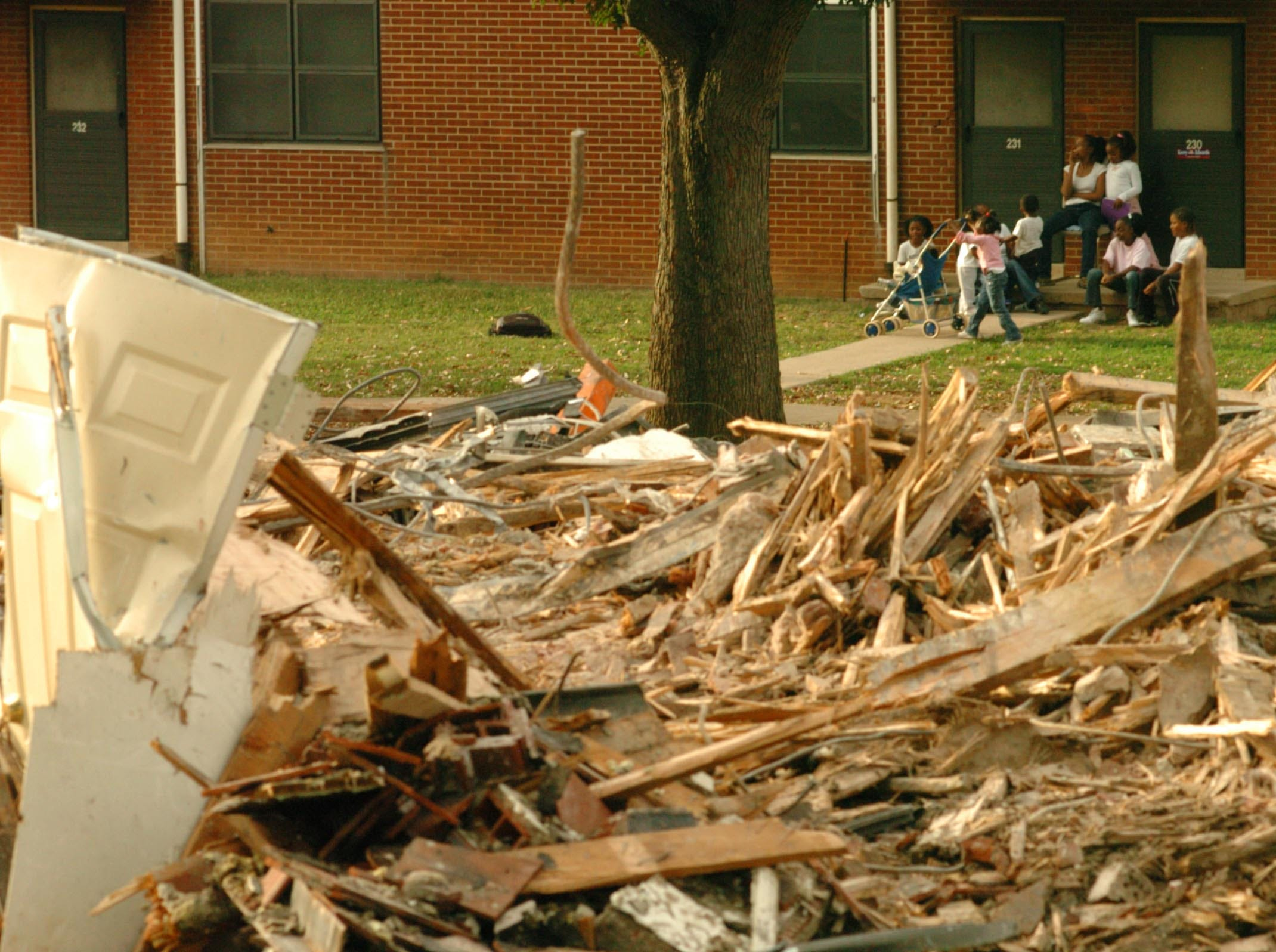 Austin Home residents sit outside one of the buildings near where some of the older Austin Homes buildings are being torn down on October, 11, 2004.
