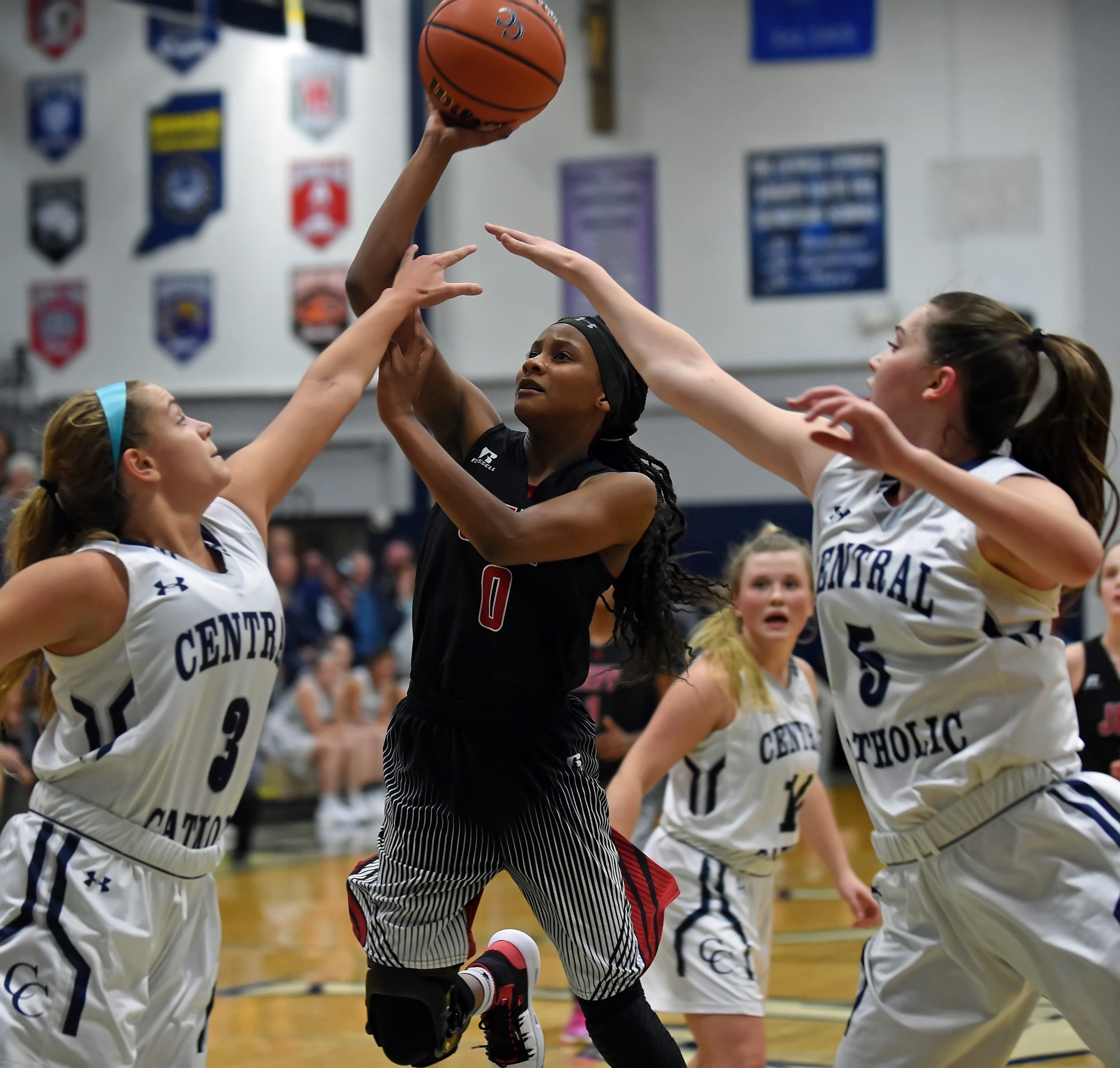 Junior point guard Kyrstin Green drives the paint for Jeff between Kaylyn Cherry and Lexi Thompson Tuesday night at Central Catholic.