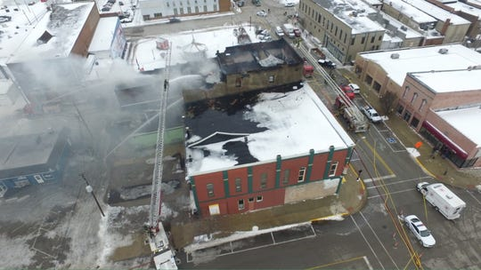 Frankfort firefighters, assisted by Lebanon firefighters, pour water onto a fire Tuesday in downtown Frankfort. One firefighter suffered minor injuries while putting out the fire, which damaged two buildings on West Washington Street.