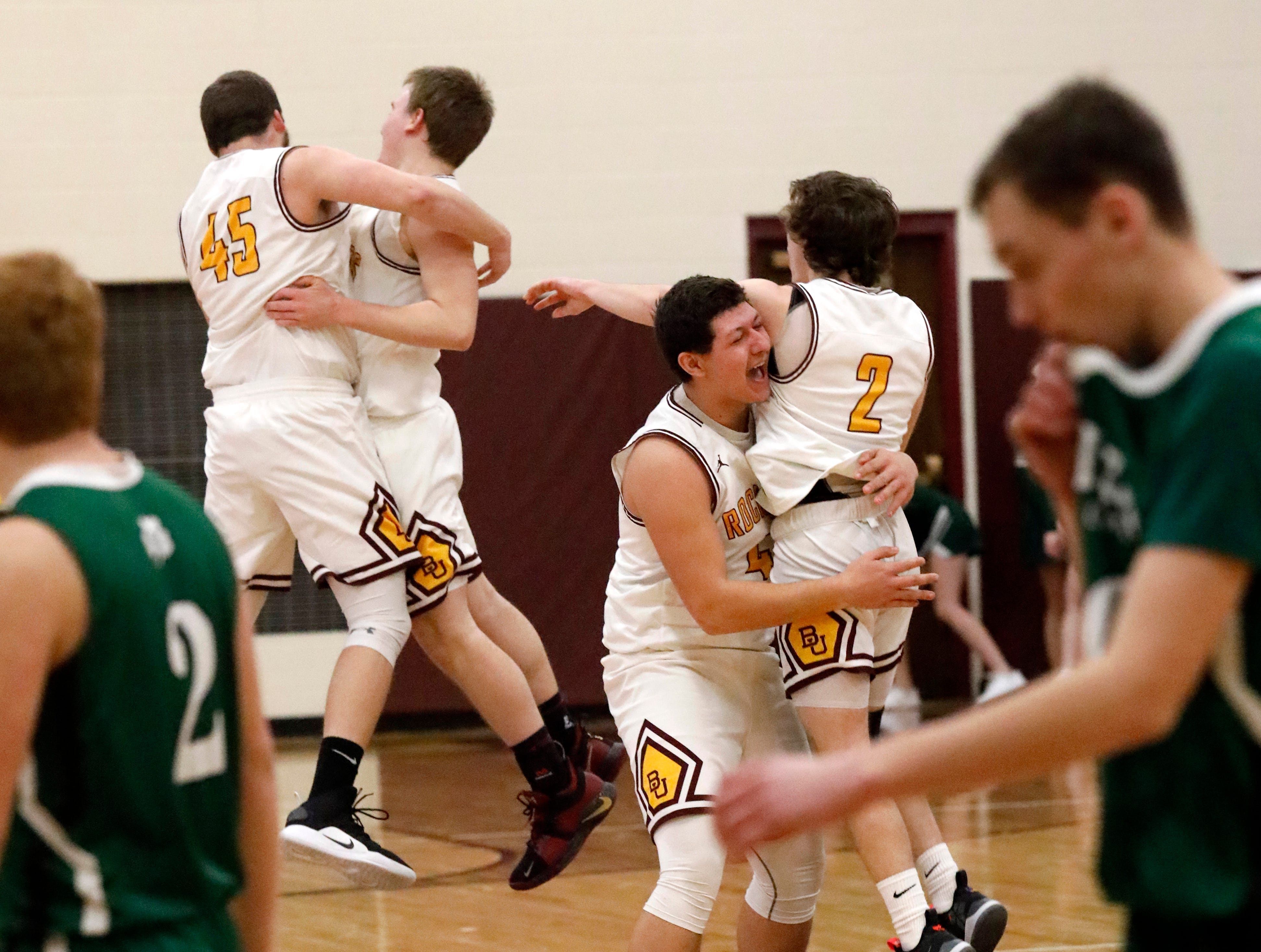 Berne Union's Baron Sullivan, far left, embraces Chase Blevens as Jacob Harmon does the same with Chase McCartney, far right, while Fisher Catholic's Carter Brady, left, and Bryson Vogel, right, walk off the court following the Rockets' 58-49 win over the Irish Tuesday night, Jan. 22, 2019, at Berne Union High School in Sugar Grove.
