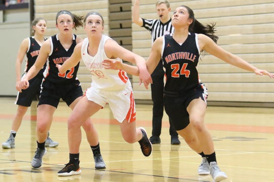 Brighton's Sydney Hetherton (center) goes for a rebound against Northville's Ellie Thallman (left) and Nicole Martin (24) on Tuesday, Jan. 22, 2019.