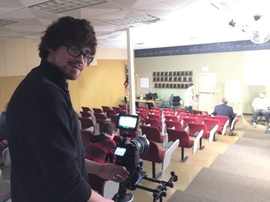David Vega adjusts camera equipment before shooting a scene in a movie he is directing about traumatic brain injury in the auditorium of RE/MAX Platinum in Genoa Township, Wednesday, Jan. 23, 2019.