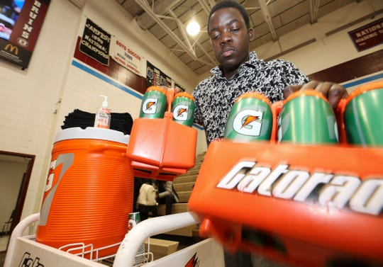 Ballard High basketball team manager Sam Ajagbe, 17, fills water bottles before their game against J-Town at Ballard High School.  The Ballard senior would like to become a team manager in the professional ranks.Jan. 22, 2019