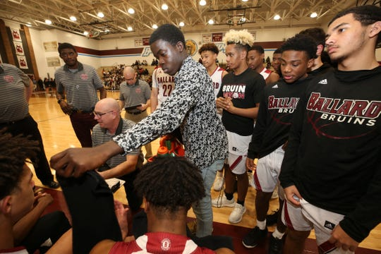 Ballard High basketball team manager Sam Ajagbe, 17, handed towels to players during a timeout in their game against J-Town at Ballard High School.  The Ballard senior would like to become a team manager in the professional ranks.Jan. 22, 2019