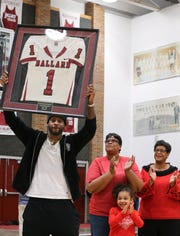 Devante Parker hoists his high school jersey at Tuesday's retirement ceremony at Ballard.