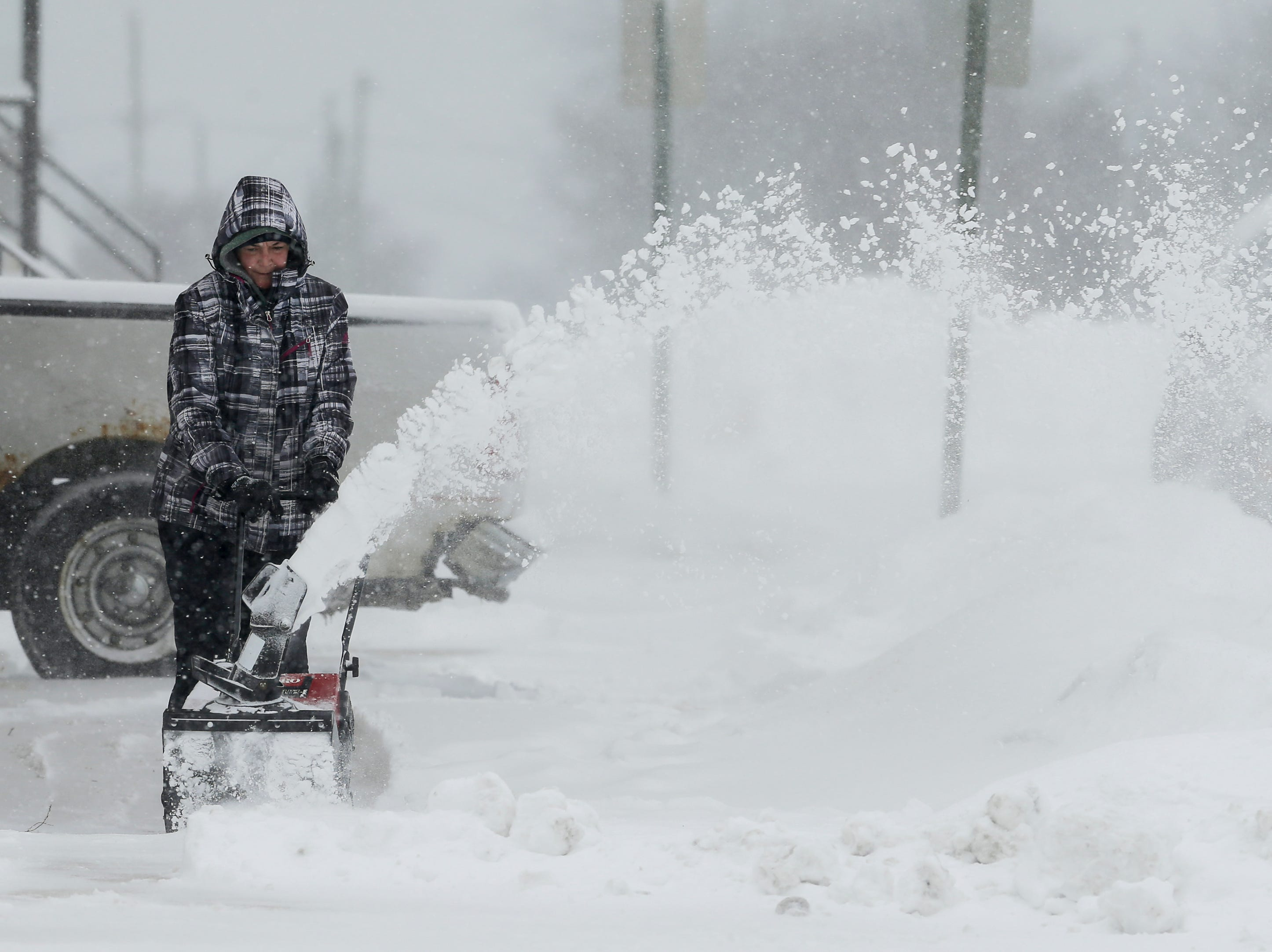 Tina Christman, of Two Rivers, clears snow from her sidewalk during a snowstorm Wednesday, January 23, 2019, in Two Rivers, Wis. Joshua Clark/USA TODAY NETWORK-Wisconsin