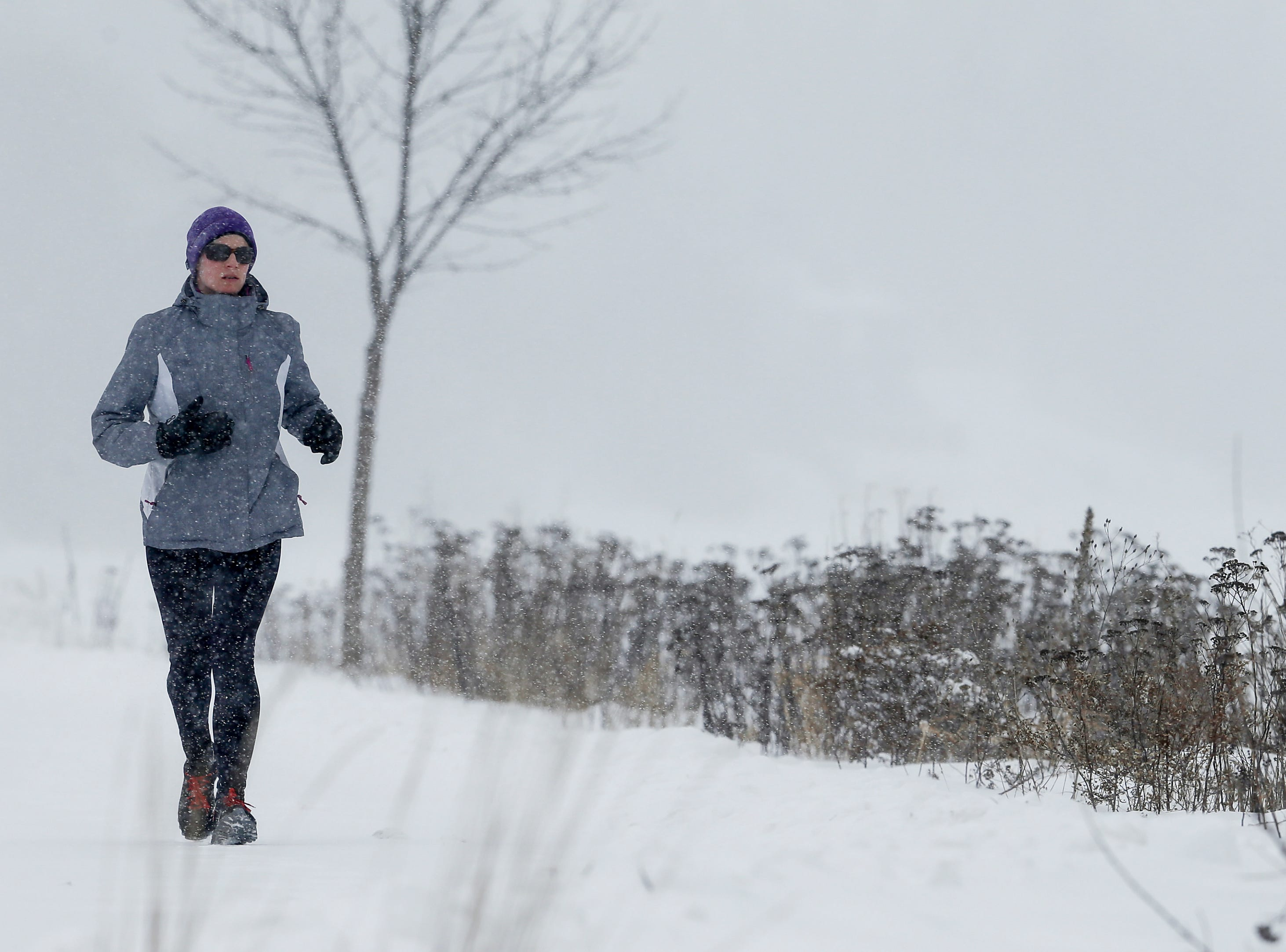 Molly Wall runs on the Mariners Trail along Lake Michigan during a snowstorm Wednesday, January 23, 2019, in Manitowoc, Wis. Joshua Clark/USA TODAY NETWORK-Wisconsin