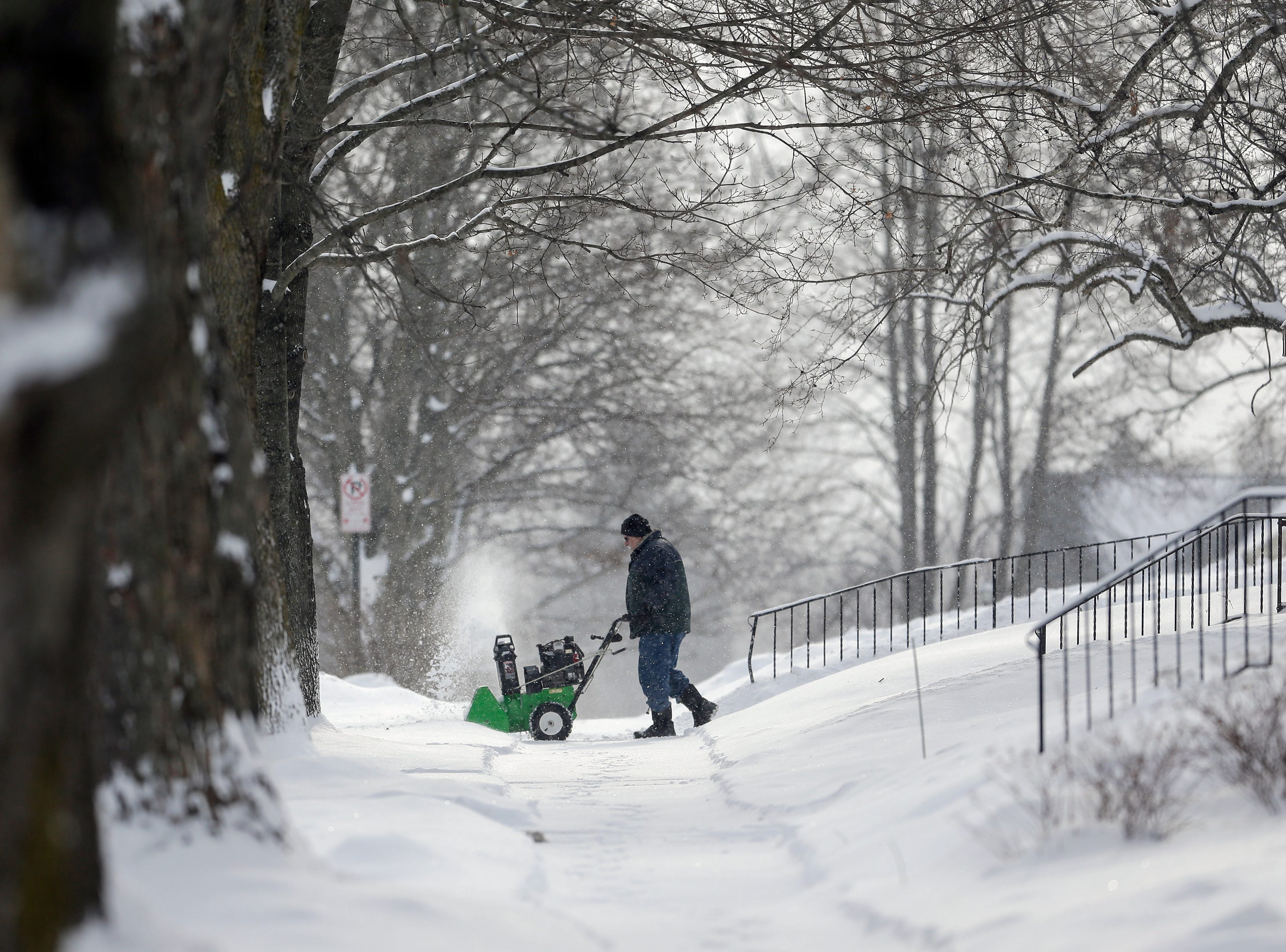 A man clears the sidewalk after a snowstorm Wednesday, January 23, 2019, in Manitowoc, Wis. Joshua Clark/USA TODAY NETWORK-Wisconsin