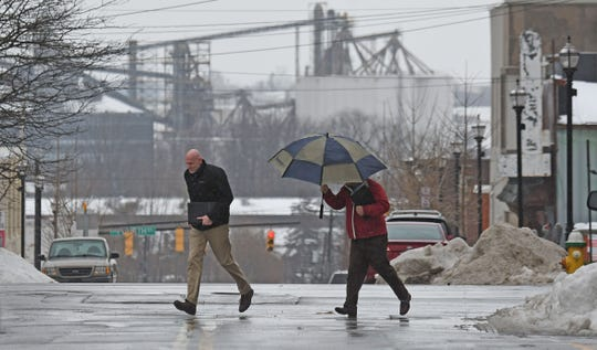 Pedestrians needed umbrellas as the rain fell in downtown Mansfield this winter in this News Journal file photo.