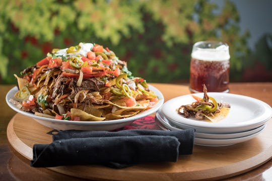 The nachos at Next Door are topped with tender brisket and sauteed peppers and onions.