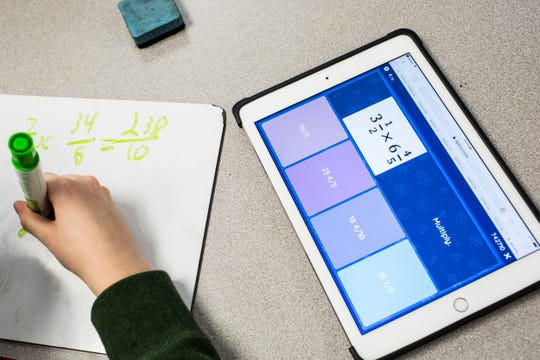 A student works out math equations using a dry erase board and an iPad in Heather Floyd's fifth-grade class Jan. 23 at Collierville Elementary School. The school was given an Apple Distinguished School Award in the fall, bestowed on schools around the world that have found ways to work the company's technology into classrooms.