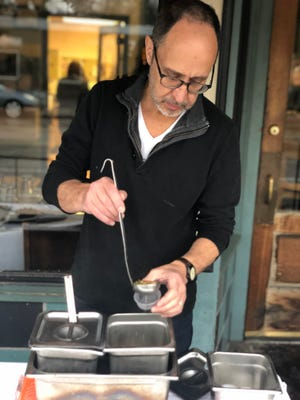 """Ben Smith, chef and owner of Tsunami Restaurant, prepares a sample of the soups he sells every Saturday morning at his """"chefs market."""""""