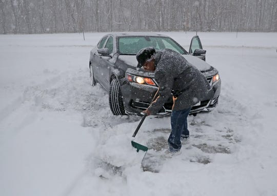 Parlene Jones shovels her car out in her driveway on Milwaukee River Parkway in Milwaukee on Wednesday. A steady overnight snow covered southern Wisconsin with several inches of snow, but the National Weather Service is saying the worst of the storm will hit the area between 5 and 11 a.m., making for a very challenging morning commute.