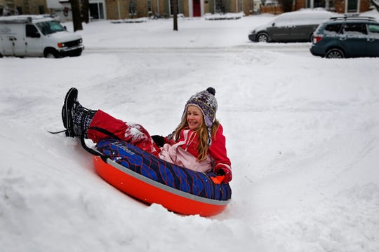 Claire Watters, 9, slides down a mound of what was previously driveway snow while playing with other neighborhood children Wednesday on Jackson Park Boulevard in Wauwatosa.