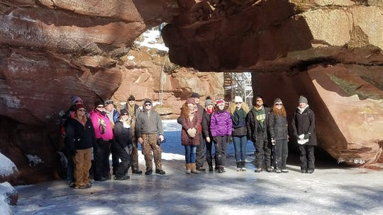 A group on a tour of the Red Cliff ice caves with Rustic Makwa Den poses for a photo beneath one of seven sea arches in the Apostle Islands archipelago.
