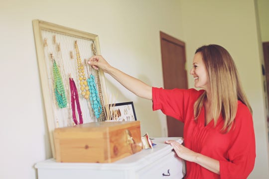 Laura Gramann Richter, owner of Pieces into Place in Elm Grove organizes accessories on a dresser.
