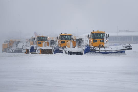 Crews remove snow Wednesday from a runway at Mitchell International Airport in Milwaukee.