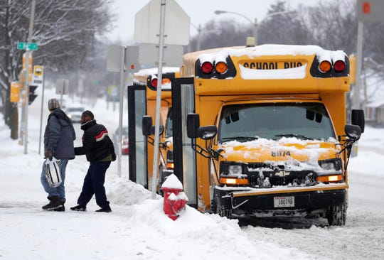 A student is escorted off a school bus at the Milwaukee School of Languages last week.